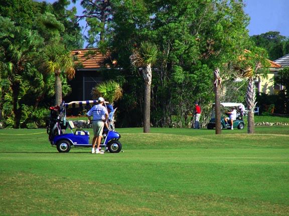 man next to golf car